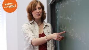Studentin steht an Tafel